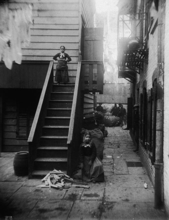 circa 1890: Two young girls, both ragpickers, stand at a staircase in Baxter Alley, Little Italy, New York City. The alley was known as 'Ragpickers Row.' (Photo by Jacob A. Riis/Museum of the City of New York/Getty Images)