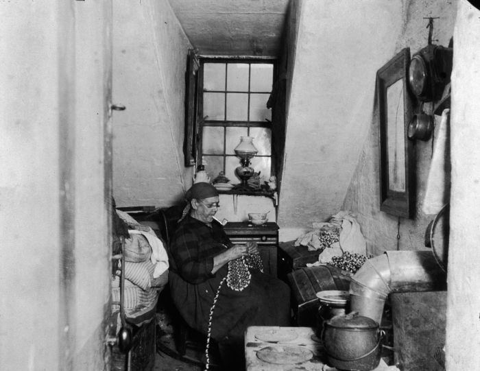 circa 1897: Mrs Benoit, a Native American widow, sews and beads while smoking a pipe in her Hudson Street apartment, New York City. (Photo by Jacob A. Riis/Museum of the City of New York/Getty Images)