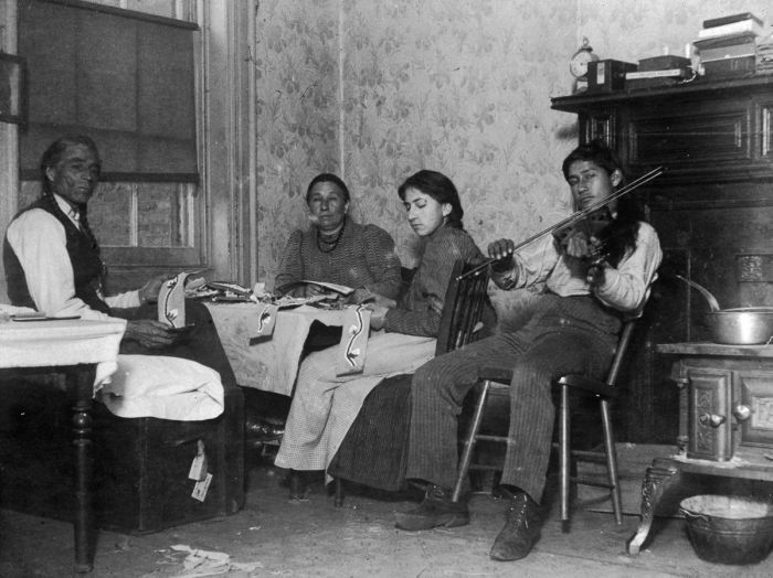 December 1895: A Native American, Mountain Eagle and his family make handicrafts while one son plays violin in their tenement at 6 Beach Street in New York City. (Photo by Jacob A. Riis/Museum of the City of New York/Getty Images)