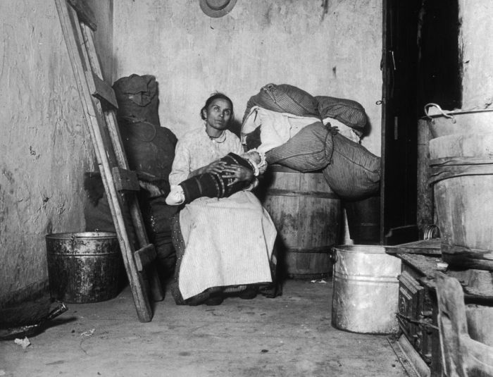 1887: An Italian immigrant rag-picker sits with her baby in a small run-down tenement room on Jersey Street, New York City. (Photo by Jacob A. Riis/Museum of the City of New York/Getty Images)